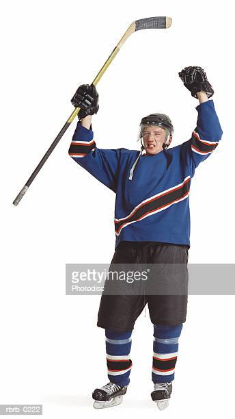 an adult caucasian male hockey player in a blue jersey raises his arms and stick to celebrate a goal - hockey stick stock pictures, royalty-free photos & images