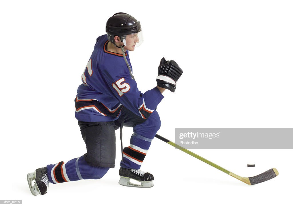 an adult caucasian male hockey player in a blue jersey speedily skates forward with his stick and puck : Stockfoto