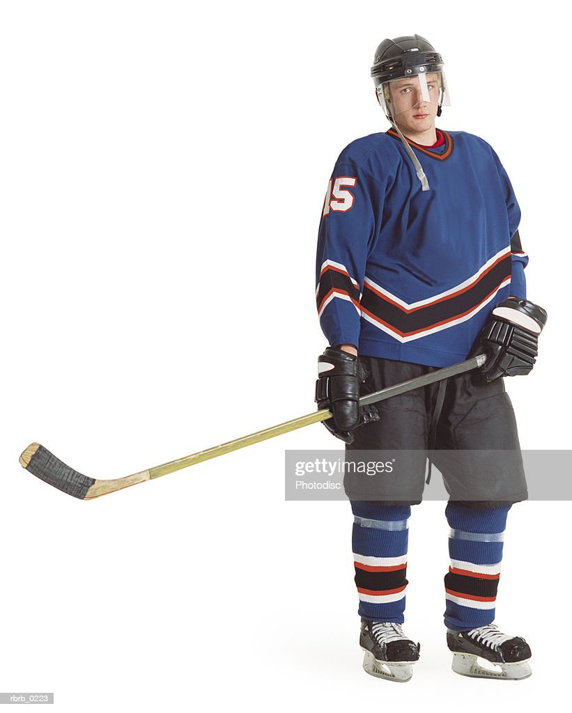 an adult caucasian male hockey player in a blue jersey stands with his stick extended and displays a stern look : ストックフォト