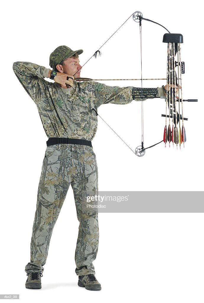an adult caucasian male hunter and archer dressed in camouflage stands and draws back his bow : Foto de stock