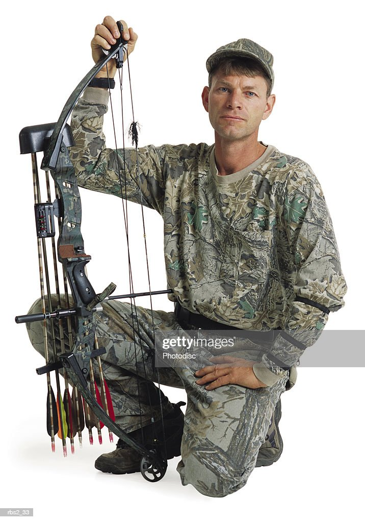 an adult caucasian male hunter and archer in camouflage kneels down with holding up his bow and arrows : Stockfoto