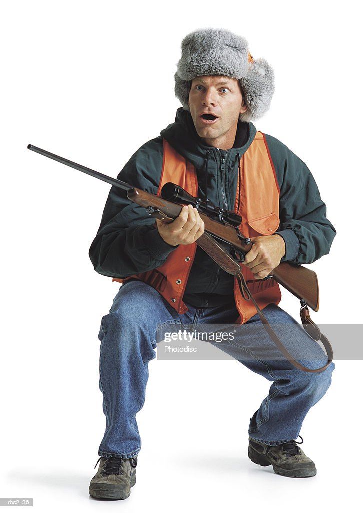 an adult caucasian male hunter in an orange vest and fuzzy hat holds his rifle as he makes a goofy expression while squatting down : Foto de stock