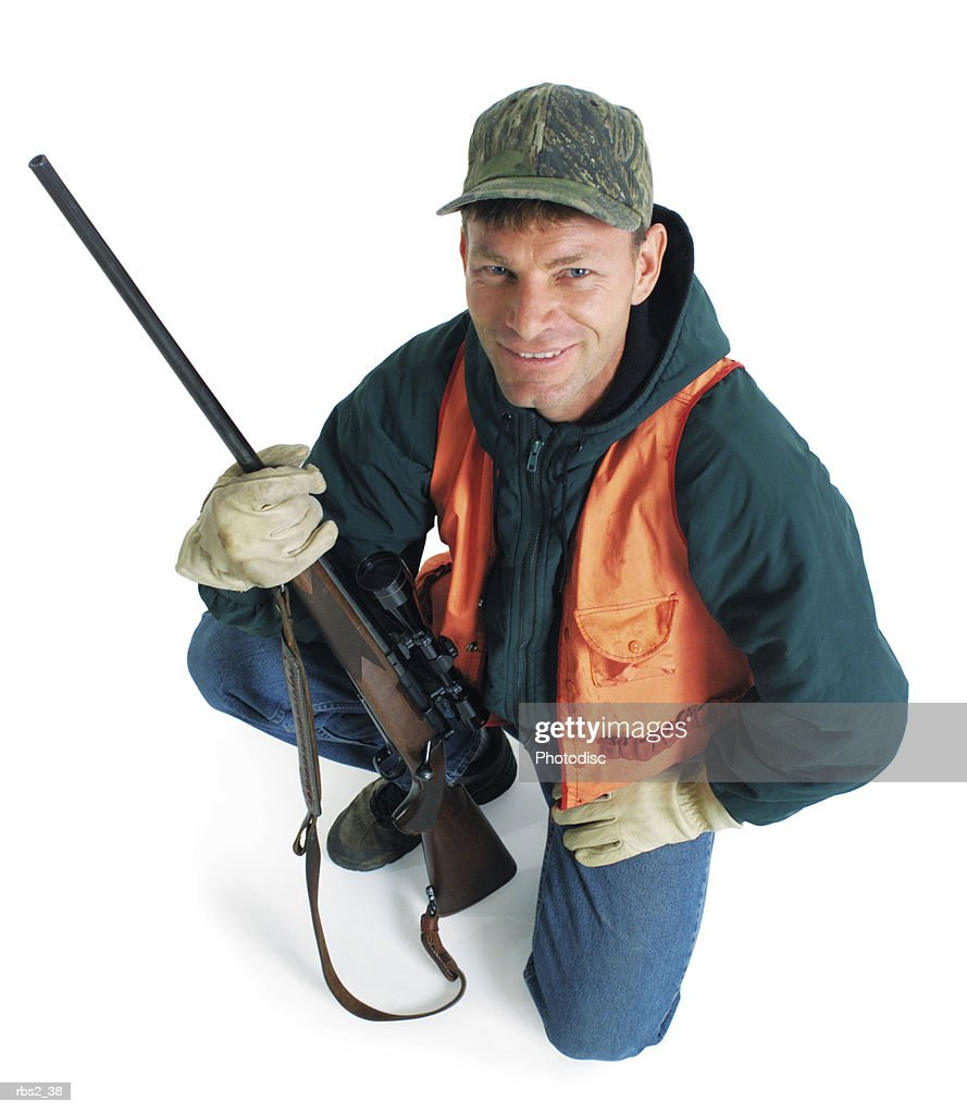 an adult caucasian male hunter wearing a green jacket and an orange vest kneels with his rifle and smiles up at the camera : Foto de stock