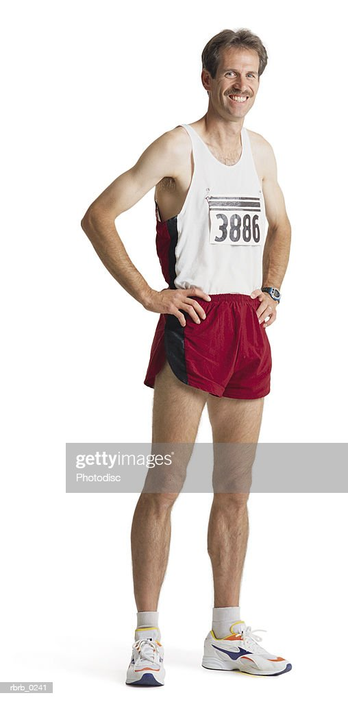an adult caucasian male marathon runner in red shorts and a white tank stands smiling with hands on hips : Stock Photo