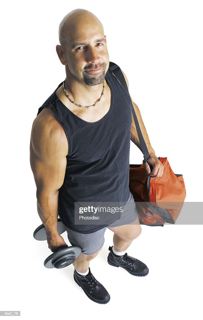 an adult caucasian male weightlifter in a black tank top holding a dumbell and his gear stands and looks up at the camera : Stock Photo