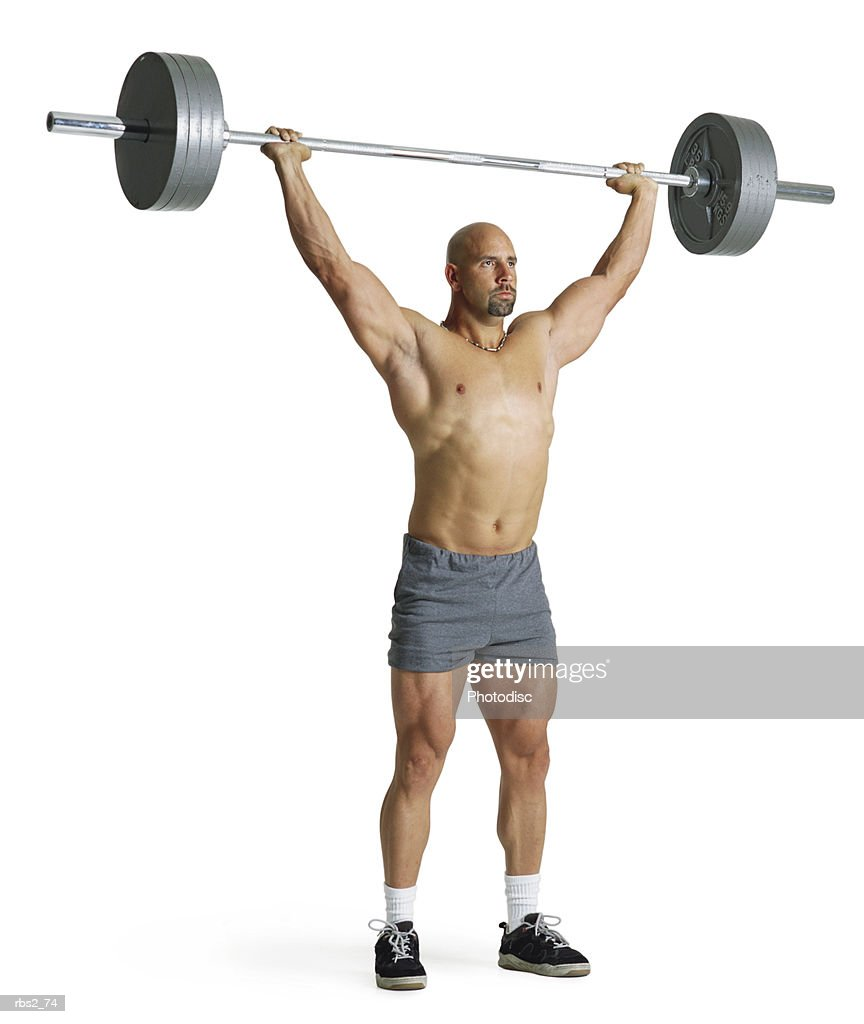 an adult caucasian male weightlifter in gray shorts stands with an extremely heavy weight raised high above his head : Foto de stock