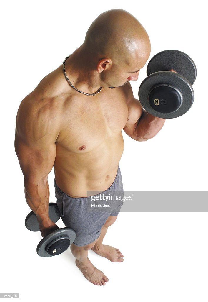 an adult caucasian male weightlifter works out his biceps by lifting dumbell weights as the camera looks down from above : Foto de stock