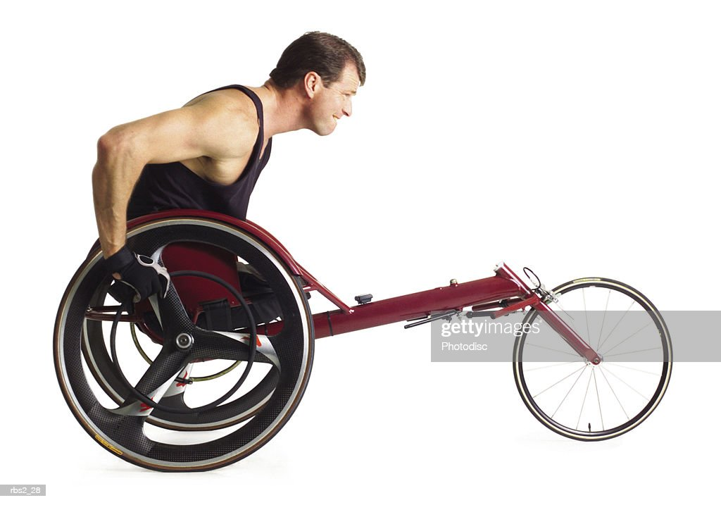 an adult caucasian male wheelchair racer in a black tank top grips his wheels and races forward : Stock Photo