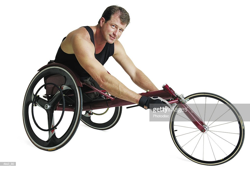 an adult caucasian male wheelchair racer in a black tank top sits in his wheelchair and grips the base : Stockfoto