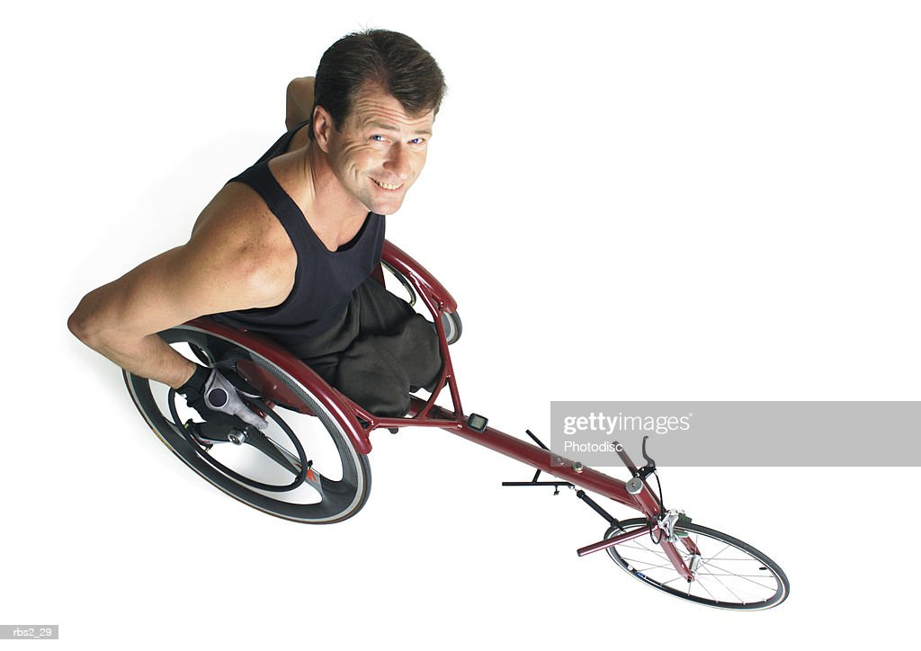an adult caucasian male wheelchair racer in a black tank top smiles as he looks up at the camera : Foto de stock