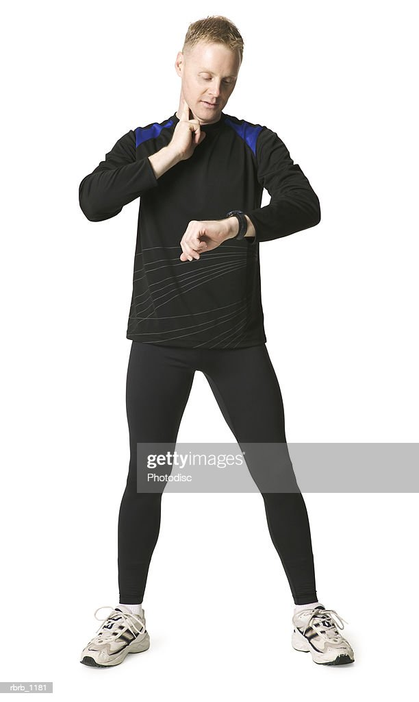 an adult caucasian man in a black running outfit checks his pulse in his neck : Stockfoto