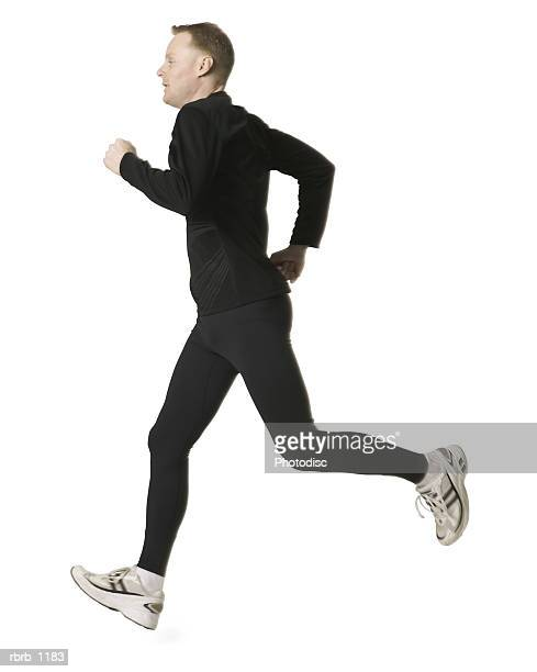 an adult caucasian man in a black running outfit jogs forward