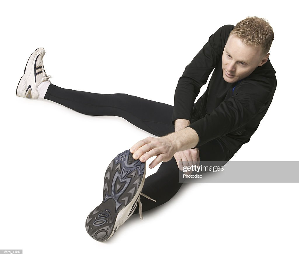an adult caucasian man in a black running outfit stretches out and prepares for a jog : Stock Photo