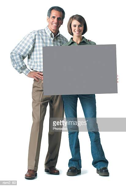 an adult caucasian man in tan pants and plaid shirt smiles with his teenage daughter as she holds up a blank sign