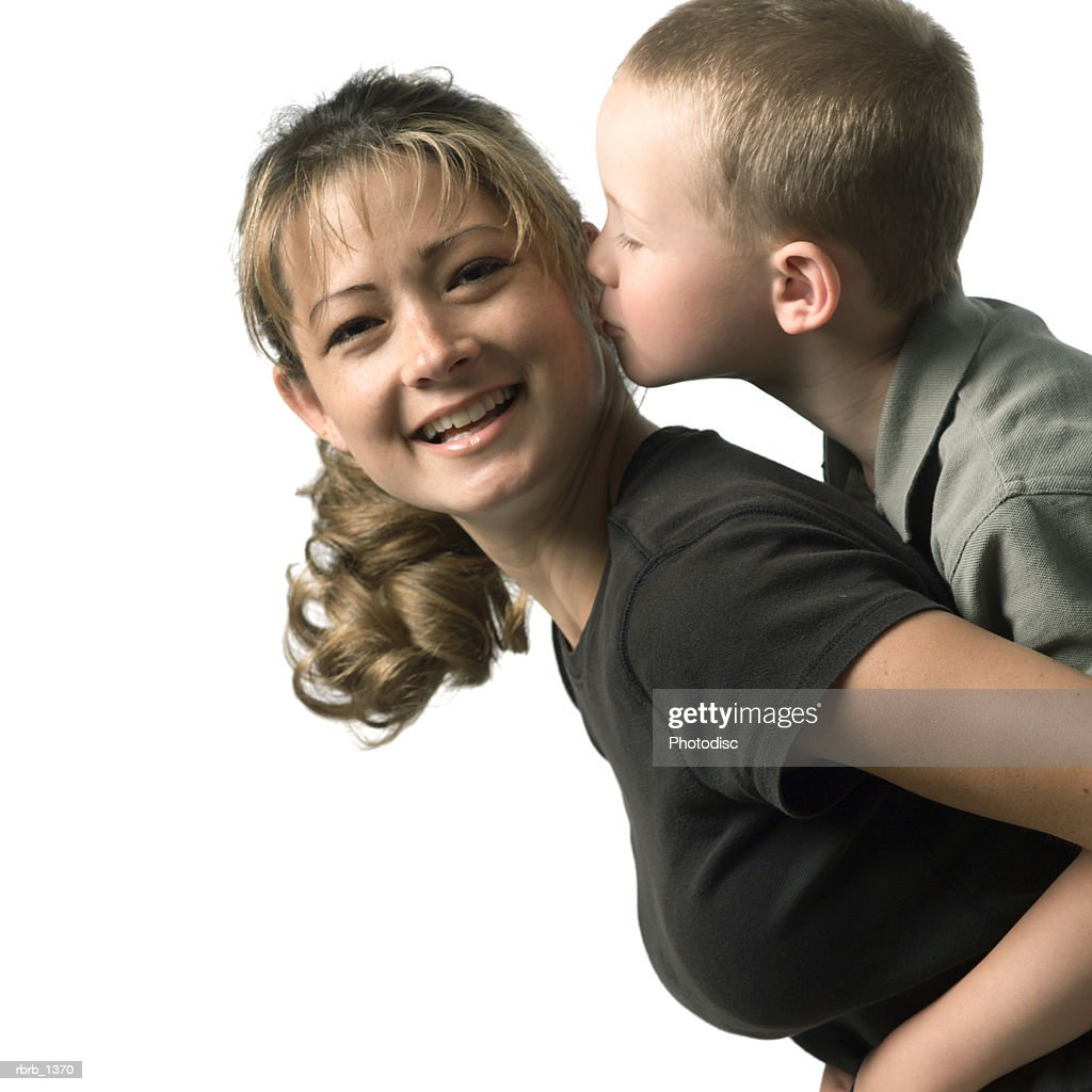 an adult caucasian mother holds her young son as he leans in to kiss her : Stockfoto