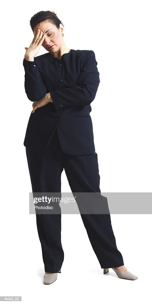 an adult caucasian woman in a dark pant suit holds her head as if stressed : Foto de stock