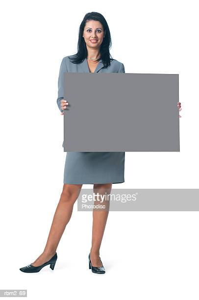 an adult ethnic female in a grey business outfit holds a blank sign out in front of herself