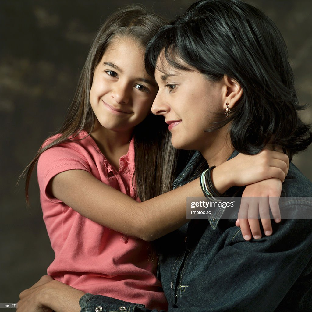 an adult ethnic mother hugs her cute young daughter as she sits on her lap : Foto de stock