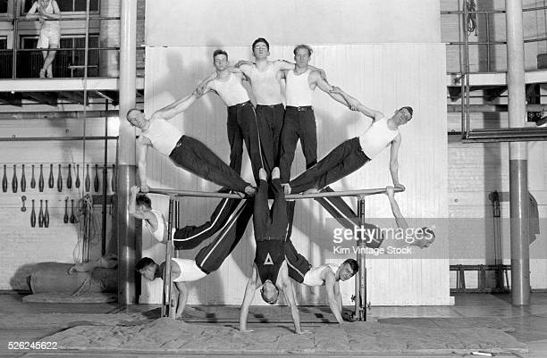 An adult gymnast club performs a group stunt on the parallel bars at the Rochester New York YMCA at the beginning of the 20th century