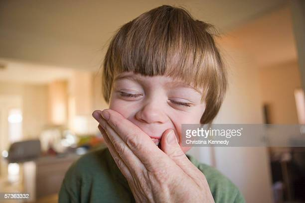 an adult hand covering a young boys mouth - christina grosse stock-fotos und bilder