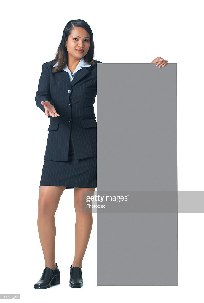 an adult hispanic woman in a blue business outfit stands by a large sign and gestures to it : Stockfoto
