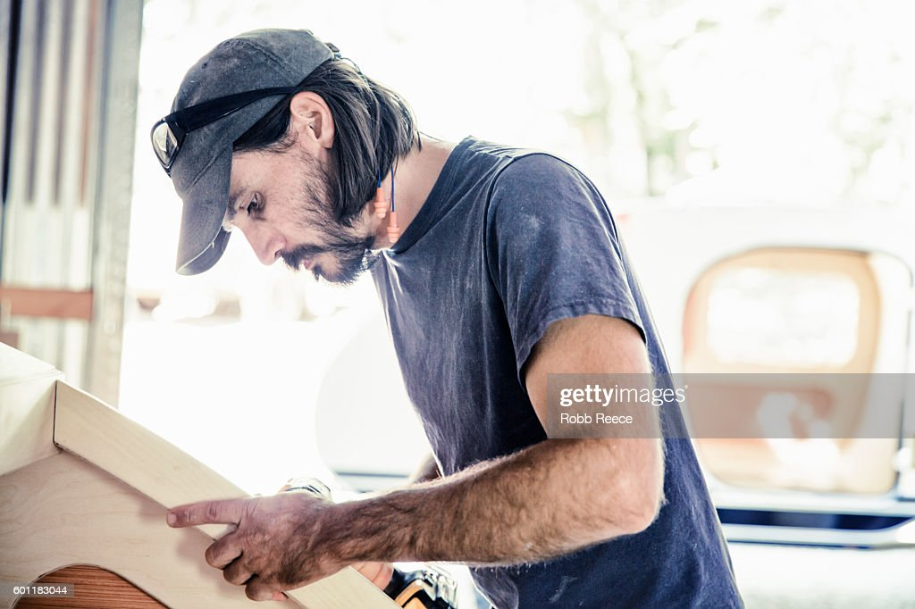 An adult, male carpenter working with tools in his wood shop : Stock Photo