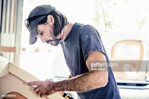 an adult, male carpenter working with tools in his wood shop - robb reece stockfoto's en -beelden