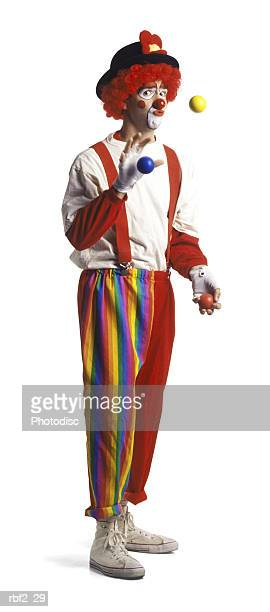 an adult male clown in a wild oufit smiles as he juggles