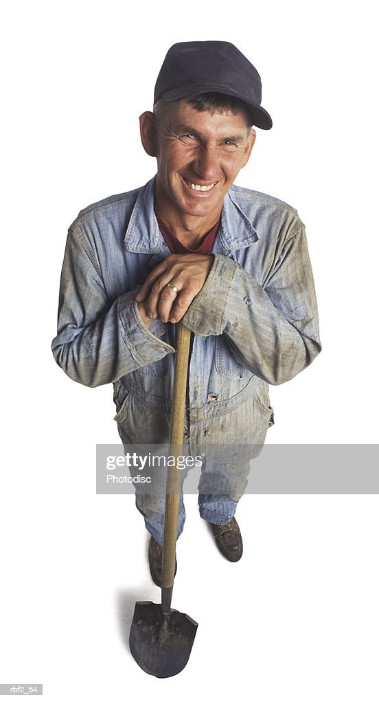 an adult male farmer in work clothes and a shovel smiles up at the camera : Stockfoto