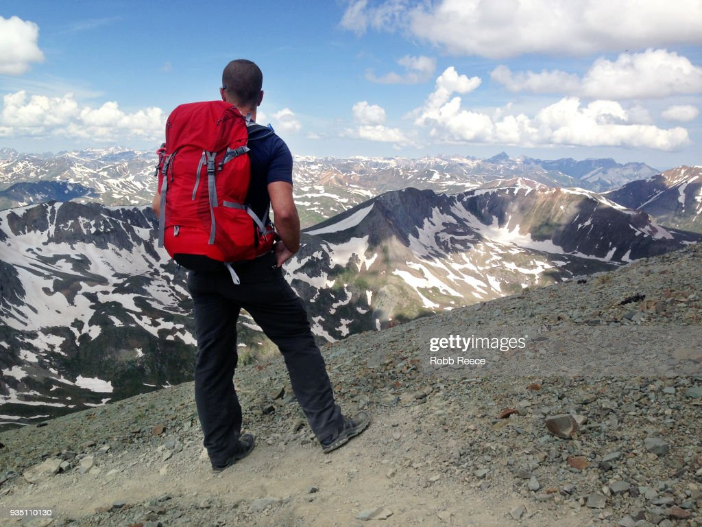 An adult male looks out over a mountain range alone on a remote mountain trail : Stock Photo