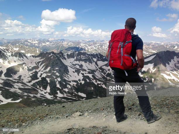 an adult male looks out over a mountain range alone on a remote mountain trail - robb reece stockfoto's en -beelden