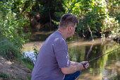 an adult man catches predatory fish
