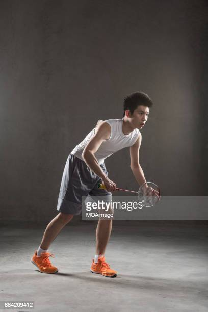 an adult man playing badminton - badminton sport stock photos and pictures