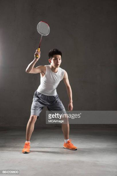 An adult man playing badminton