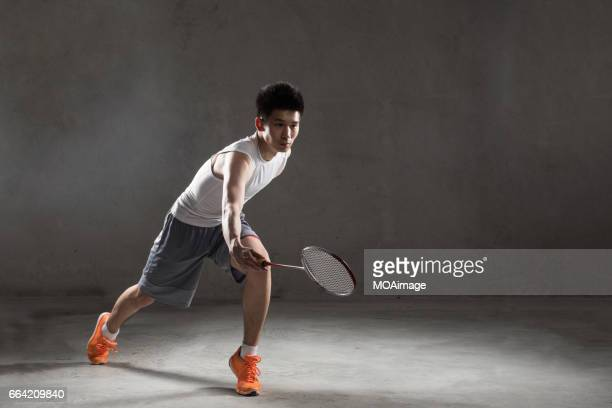 An adult man playing badminton