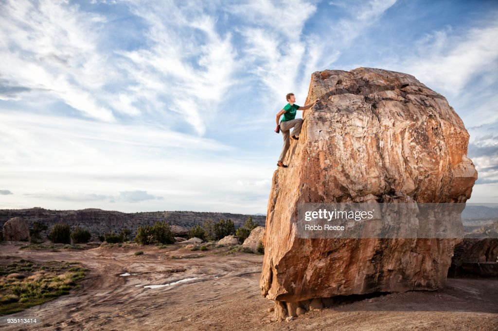 An adult man rock climbing on a rock in the desert : Stock Photo