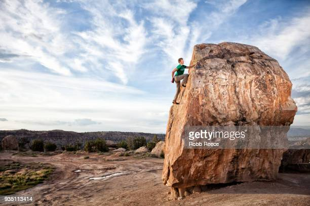 an adult man rock climbing on a rock in the desert - robb reece stock pictures, royalty-free photos & images