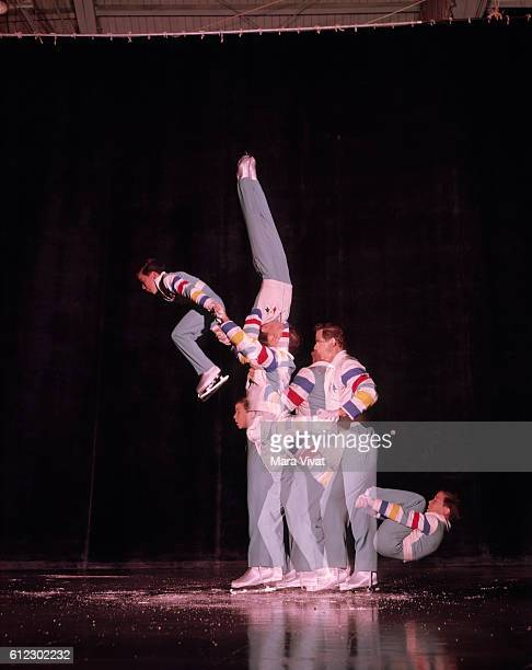An adult skater lifts a young boy over his head in the Ice Capades