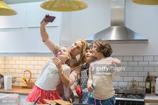 An adult woman and three children taking a selfy photograph in the kitchen.