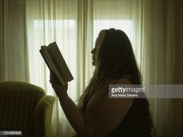 an adult woman reading a hardcover book next to a curtained window in vintage style - authors imagens e fotografias de stock