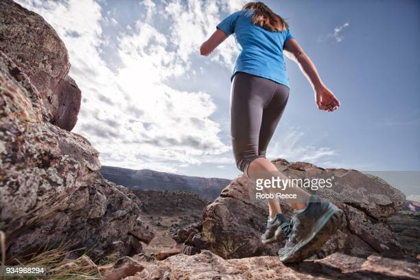 an adult woman trail running on a remote dirt trail - robb reece stockfoto's en -beelden