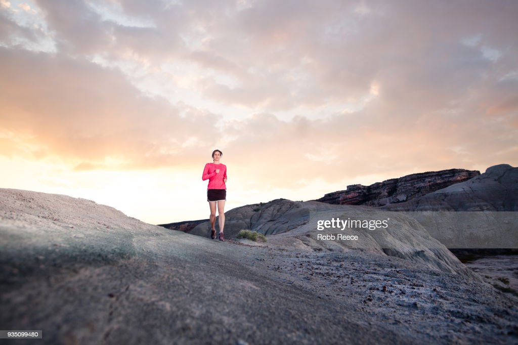 An adult woman trail running on a remote dirt trail : Stock Photo