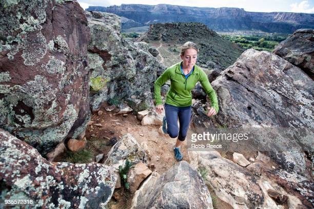 an adult woman trail running on a remote dirt trail - robb reece stock pictures, royalty-free photos & images