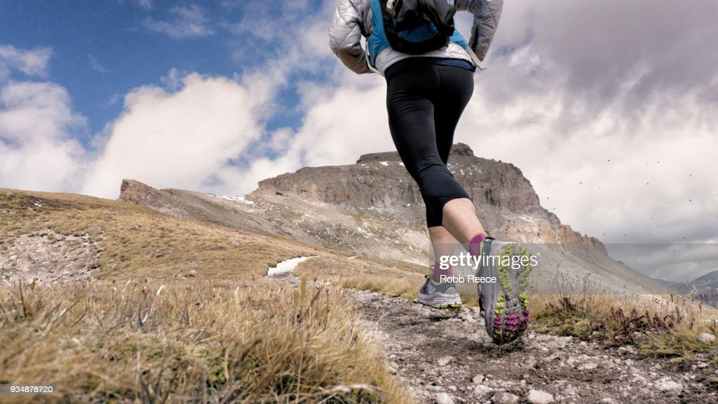 An adult woman trail running on a remote mountain trail : Stock Photo