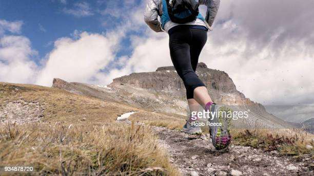 an adult woman trail running on a remote mountain trail - robb reece stock-fotos und bilder