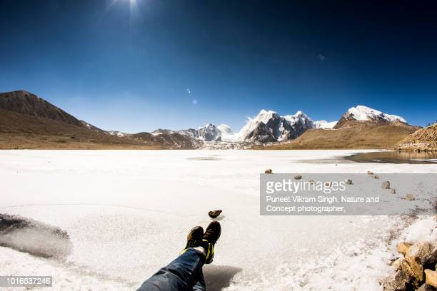 An adventurous young man lying on snow in personal point of view