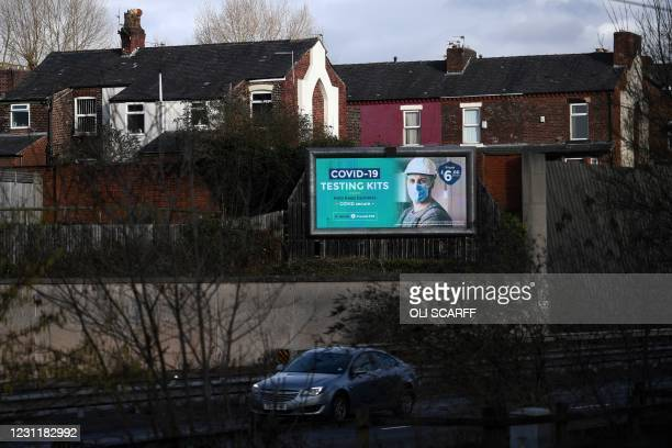 An advert for a private lateral flow Covid-19 test is pictured on a billboard near a road in Manchester, northern England, on February 15, 2021. -...