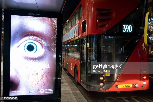 An advert from TFL featuring a dilated pupil is displayed next to a London bus in Victoria, on 2nd February 2021, in London, England.