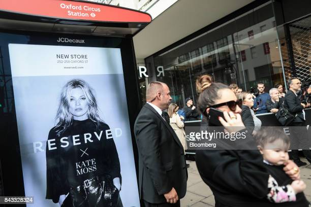 An advertisement featuring British fashion model Kate Moss stands on display on the side of a bus stop outside London's first Reserved store operated...