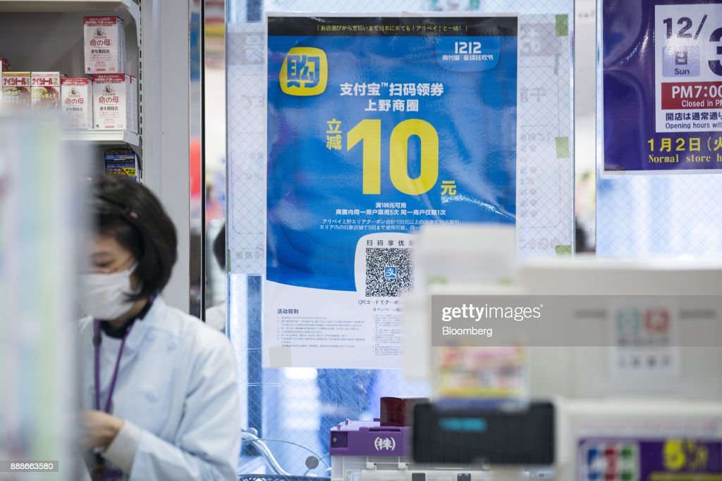 An advertisement for Ant Financial Services Group's Alipay, an affiliate of Alibaba Group Holding Ltd., is displayed at a Takeya Co. Ueno Select shop in Tokyo, Japan, on Saturday, Dec. 9, 2017. Ant Financial and its strategic partners outside China should be able to nearly double users of their payments systems in coming years, Ant's overseas operations president Douglas Feagin said on Nov. 14. Photographer: Shiho Fukada/Bloomberg via Getty Images